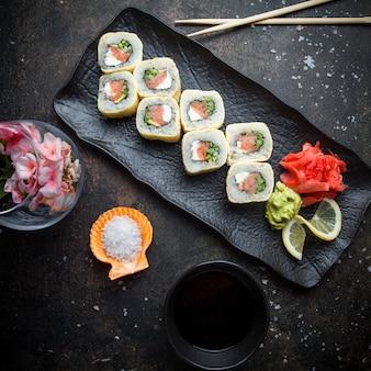 Vista superior de sushi con jengibre encurtido y wasabi y salsa de soja y palillos en plato oscuro