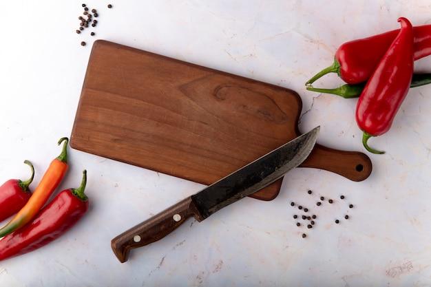 Vista superior de la tabla de cortar con cuchillo y pimientos y especias de pimienta sobre fondo blanco.
