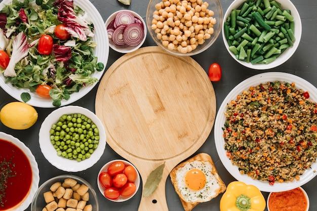 Vista superior de la tabla de cortar con huevo frito y judías verdes