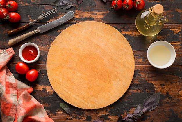 Vista superior de la tabla de cortar de pizza en la mesa de madera