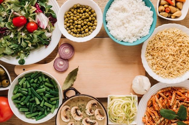 Vista superior de la tabla de cortar y platos con cebolla y ajo.