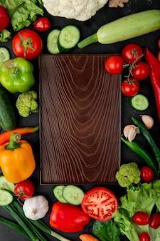 Vista superior de la tabla de cortar con verduras como pimiento, tomate, calabacín, ajo y otros alrededor sobre fondo negro