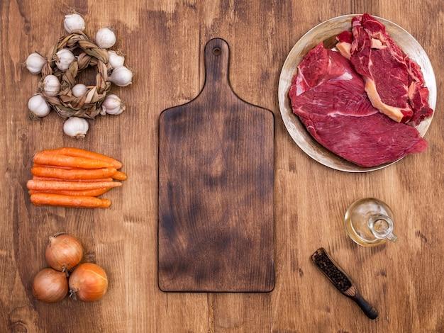 Vista superior de la tabla de cortar vintage junto a dos trozos de carne roja en la mesa de madera. zanahorias naranjas. frijoles de pimienta.