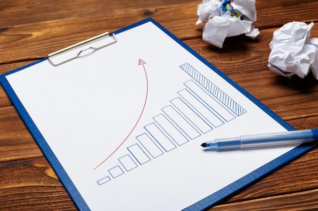 Vista superior de la tabla de papel comercial o gráfico en la mesa de madera