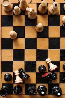 Vista superior del tablero de ajedrez antiguo con un conjunto de piezas de madera en blanco y negro de pie en posición caótica
