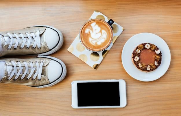 Vista superior de tablero de madera con teléfono, café