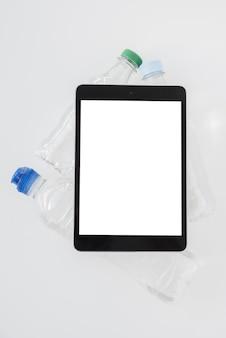 Vista superior tablet con botellas de agua