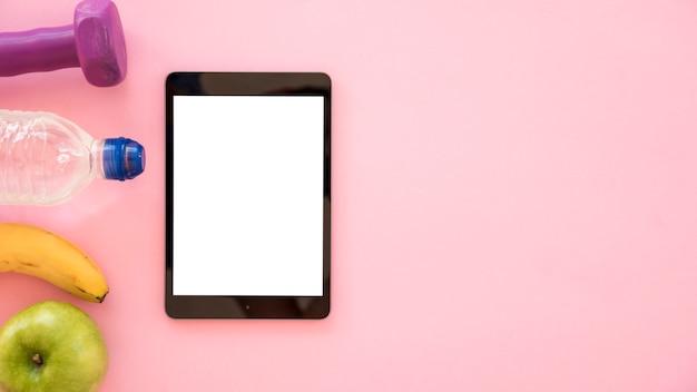 Vista superior tablet con fila de cosas saludables