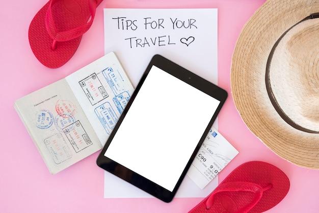 Vista superior tablet rodeada de elementos de viaje