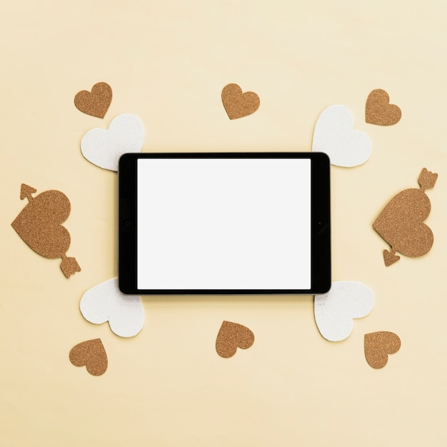 Vista superior de la tableta digital con adhesivo de corazón blanco y dorado en superficie beige