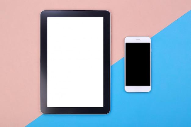 Vista superior de la tableta de la maqueta y el teléfono inteligente sobre fondo rosa y azul pastel