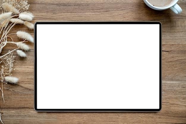 Vista superior de la tableta de la pantalla en blanco en el escritorio de oficina de madera del fondo.