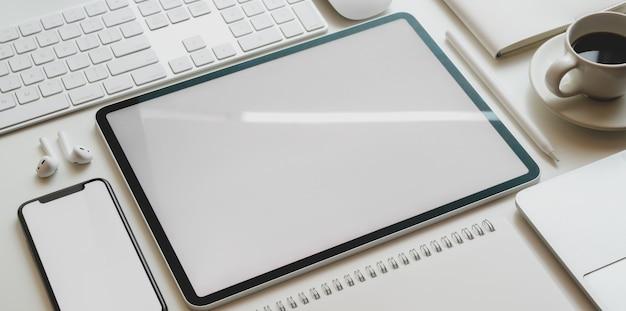 Vista superior de la tableta de pantalla en blanco y el teléfono inteligente con material de oficina en estilo moderno de oficina