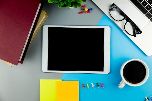 Vista superior con tableta simulada en blanco en el espacio de trabajo de escritorio de oficina.