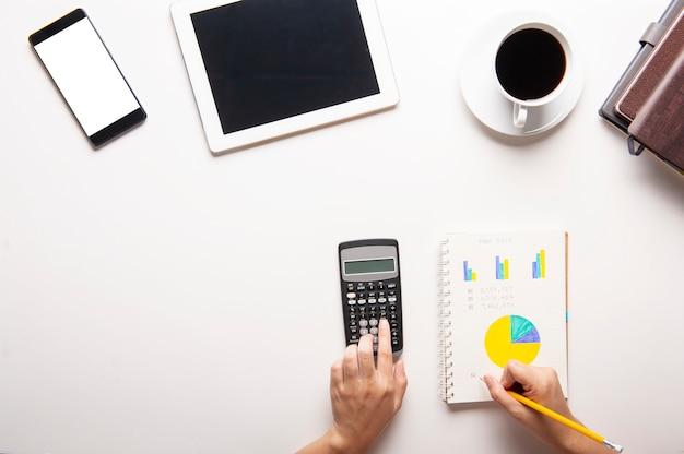Vista superior de la tableta, teléfono inteligente, calculadora, cuaderno y una taza de café sobre fondo blanco