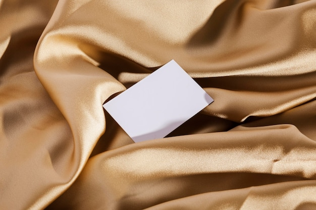 Vista superior de la tarjeta blanca sobre tela dorada