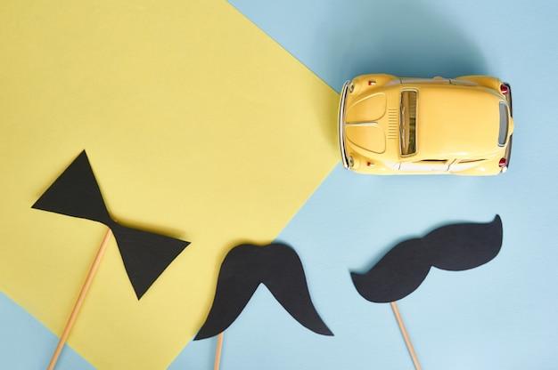 Vista superior de la tarjeta de felicitación con carro de juguete amarillo y bigote de papel negro