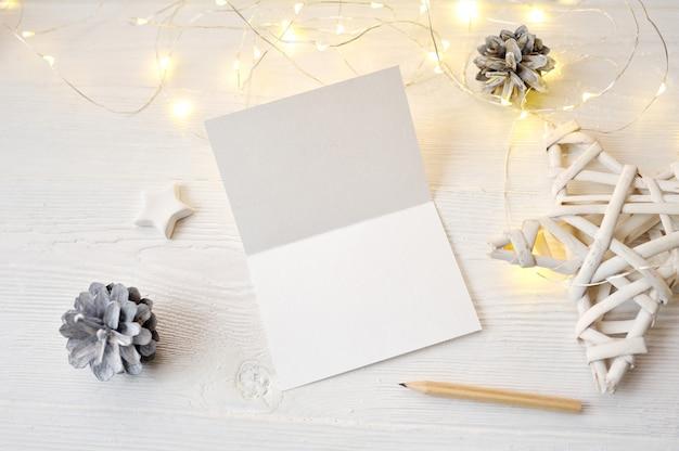 Vista superior de la tarjeta de felicitación de navidad de maqueta, flatlay sobre una madera blanca