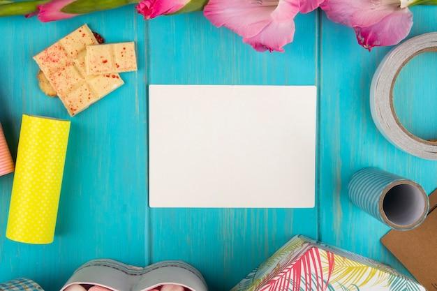 Vista superior de la tarjeta de felicitación de papel en blanco con flor de gladiolo de color rosa y chocolate blanco en la mesa de madera azul