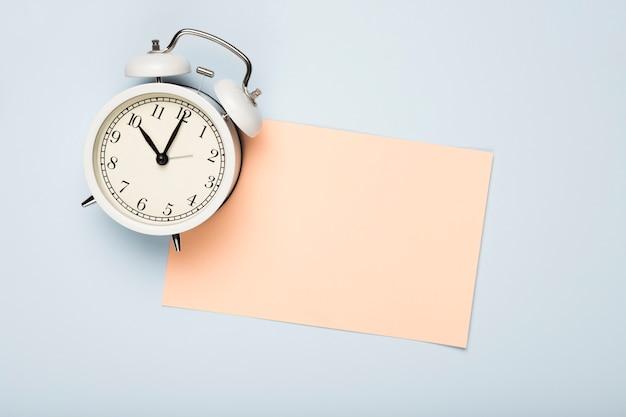 Vista superior de la tarjeta de felicitación y el reloj en la mesa