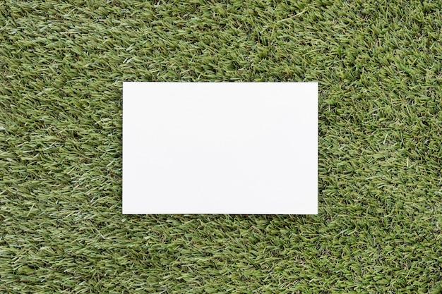 Vista superior de la tarjeta vacía en la hierba verde