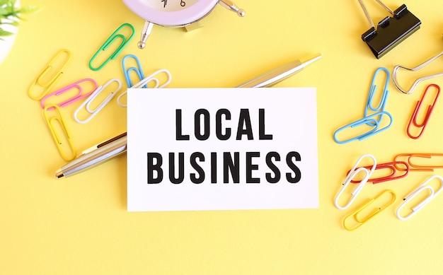 Vista superior de una tarjeta de visita con negocios locales de texto sobre un fondo amarillo