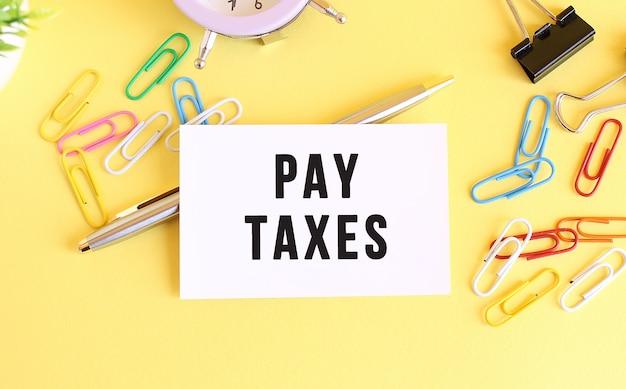 Vista superior de una tarjeta de visita con texto pagar impuestos, bolígrafo, clips y reloj
