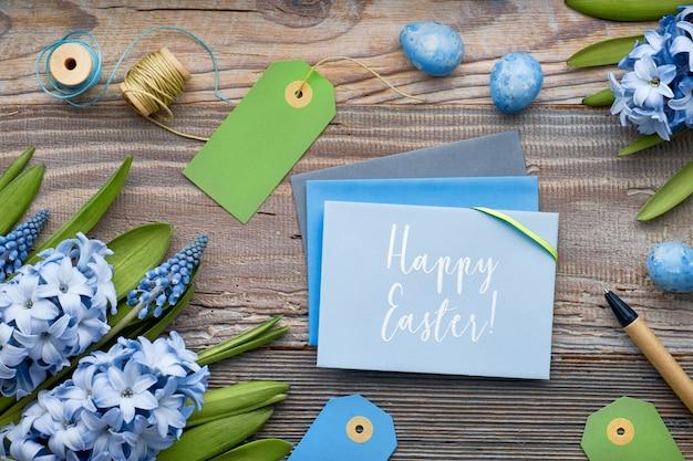 Vista superior de tarjetas de papel, flores de jacinto azul y huevos de pascua en madera rústica, texto