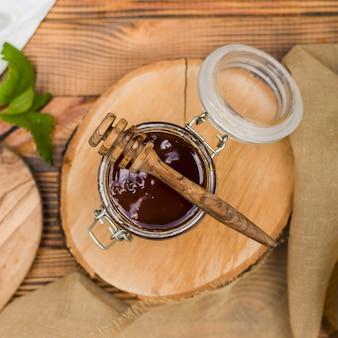Vista superior tarro de cristal lleno de miel con cuchara de miel