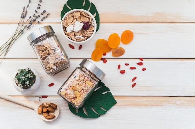Vista superior del tarro de granola y copos de maíz cerca de frutos secos y plantas suculentas sobre fondo de madera