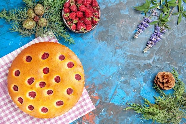 Vista superior de la tarta de frambuesa en el cuenco de toalla de cocina con rama de árbol de pino frambuesas sobre superficie azul
