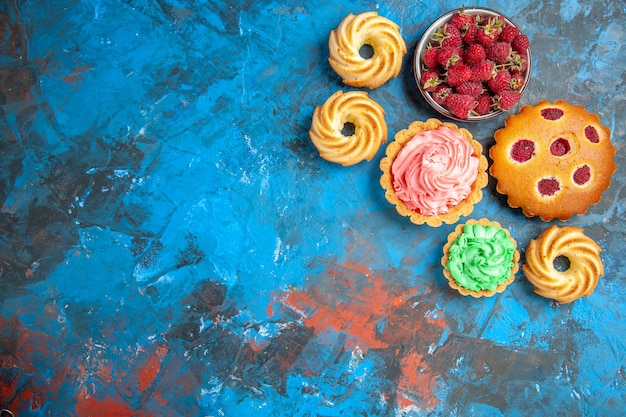 Vista superior de tarta de frambuesa, tartas pequeñas, galletas y tazón con frambuesas en superficie rosa azul