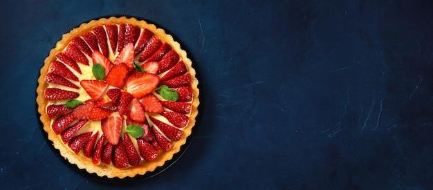 Vista superior de tarta de fresa fresca sobre fondo azul oscuro de moda