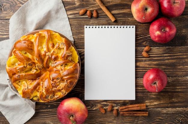 Vista superior tarta de manzana y fruta que rodea el cuaderno de notas vacío