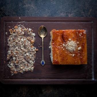 Vista superior tarta con migas de nuez y cuchara antigua en tablero de alimentos