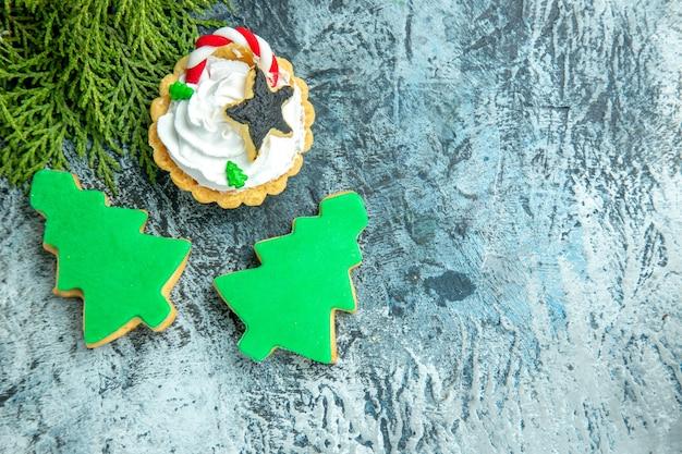 Vista superior de la tarta de navidad de la rama de pino galletas de árbol de navidad en la mesa gris lugar libre