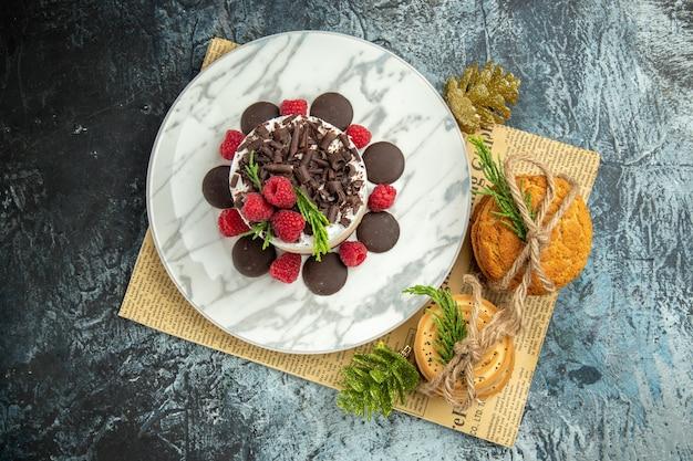 Vista superior de tarta de queso con chocolate y frambuesas en plato ovalado blanco galletas atadas en adornos navideños de periódico en superficie gris