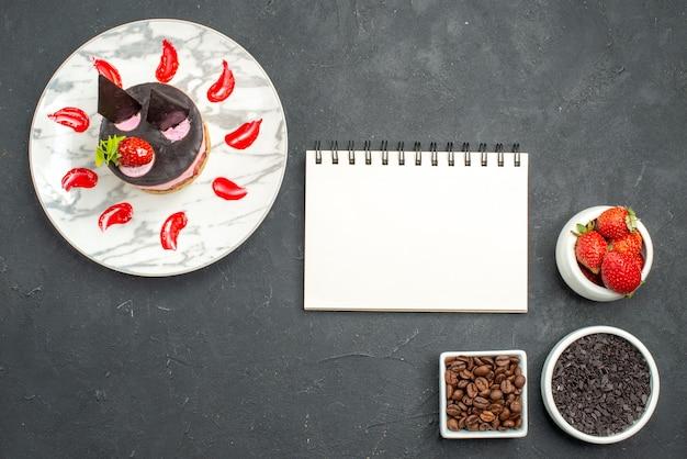 Vista superior de tarta de queso de fresa en cuencos de placa ovalada con fresas, chocolate, semillas de café, un bloc de notas sobre una superficie oscura