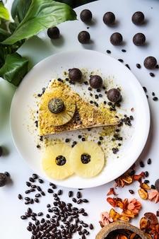 Vista superior tarta de queso con piña y bolas de chocolate en un plato
