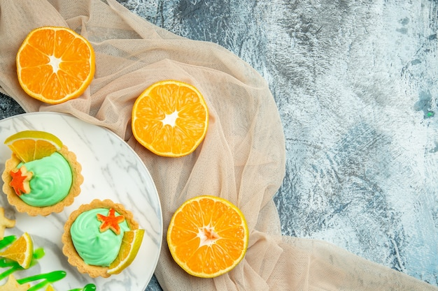 Vista superior de tartas pequeñas con crema pastelera verde y una rodaja de limón en un plato sobre un chal beige cortado naranjas en un espacio libre de mesa oscura