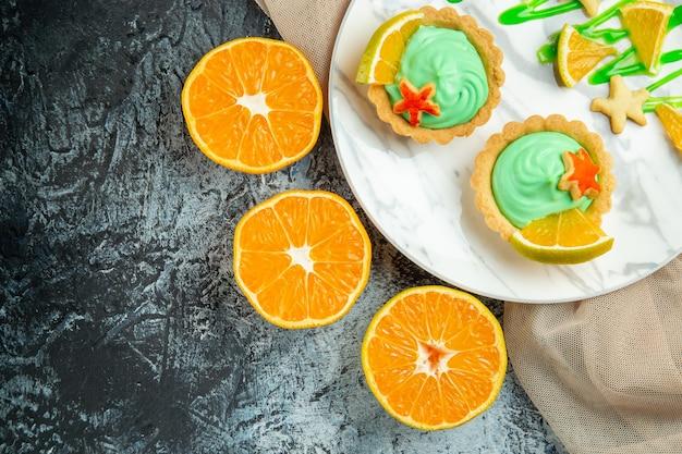 Vista superior de las tartas pequeñas con crema pastelera verde y una rodaja de limón en un plato sobre un chal beige cortado naranjas en un lugar oscuro para copiar la mesa