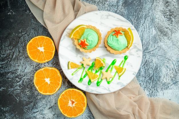 Vista superior de tartas pequeñas con crema pastelera verde y rodaja de limón en un plato sobre naranjas cortadas con mantón beige en la mesa oscura