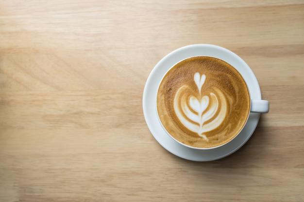 Vista superior de la taza blanca de espuma de leche de arte latte de café caliente en forma de corazón