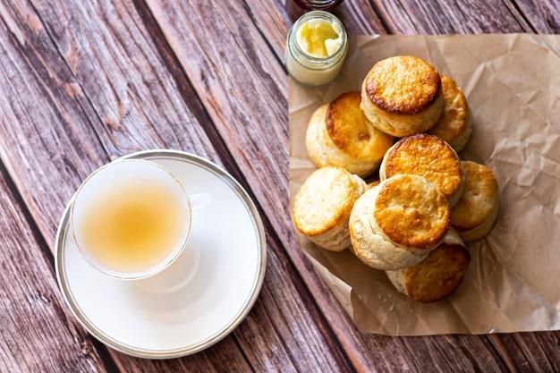 Vista superior de una taza blanca de té y bollos británicos tradicionales en la mesa de madera, desayuno comida teatime.