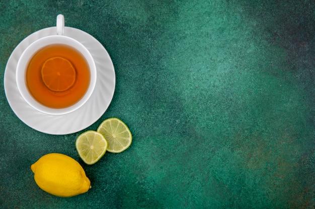 Vista superior de la taza blanca de té con limones frescos en superficie verde