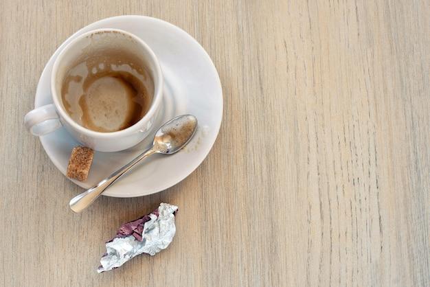 Vista superior de la taza blanca vacía después del café con algunas marcas de suciedad, restos de comida y envoltura del caramelo