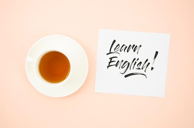 Vista superior taza de café al lado para aprender inglés nota adhesiva maqueta