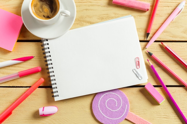 Vista superior, taza de café con café, bolígrafo poniendo en cuaderno en blanco,