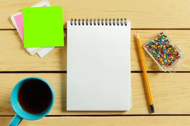 Vista superior. taza de café con café. pluma poniendo en el cuaderno en blanco.