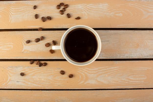 Vista superior de una taza de café caliente y fuerte con semillas de café marrón fresco en el escritorio rústico crema café semilla bebida foto grano